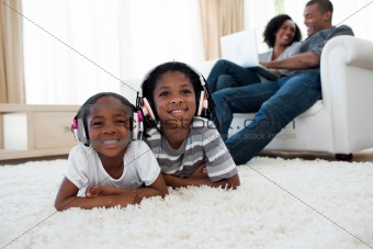 Siblings listening music lying on the floor