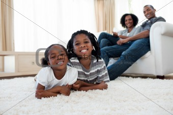 Smiling brother and sister lying on the floor