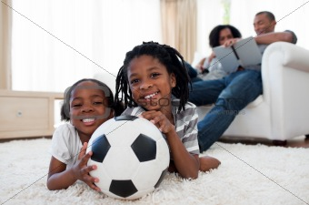 Little boy and his sister holding soccer ball
