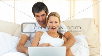 Affectionate couple using a laptop lying in the bed