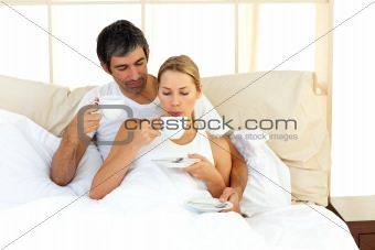 Affectionate couple drinking coffee lying in the bed at home