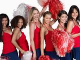 Happy cheerleaders posing against white