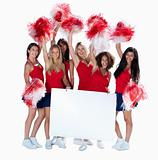 Happy cheerleaders holding an empty billboard for you text