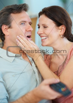 Man ignoring woman while watching TV