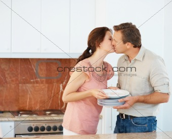 Middle aged couple kissing while doing household chores