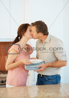 Couple kissing in the kitchen during household chores