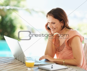 Happy mature woman using a laptop while on the phone