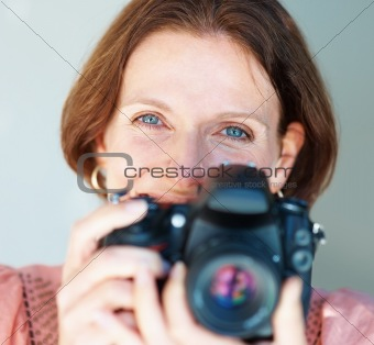 Closeup of a smiling mature woman with a SLR camera