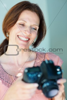 Happy middle aged woman holding a SLR camera