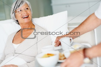 Senior relaxed female in bed being served breakfast