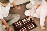Senior couple playing backgammon on the floor
