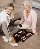 Elderly couple playing backgammon while on floor
