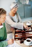 Elderly couple playing backgammon while at the breakfast table