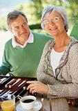 Retired couple at the breakfast table with a game of backgammon