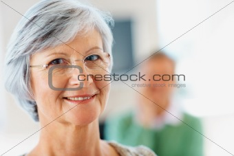 Closeup of a smiling elderly woman with a man at the back