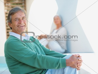 Smiling man with a woman in the background