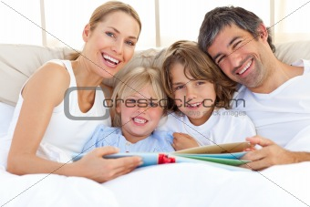 Smiling family reading a book on bed