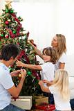 Happy family decorating Christmas tree