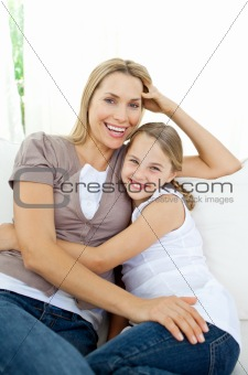 Beautiful little girl hugging her smiling mother