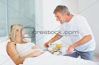 Husband serving breakfast to pregnant woman at the bed