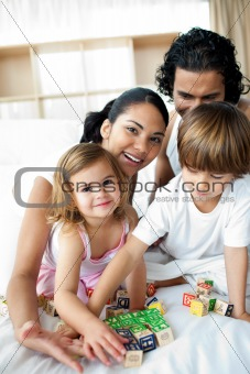Portrait of a happy family playing with letter blocks