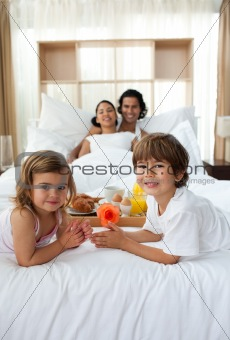 Siblings having breakfast with their parents