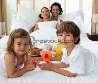 Smiling family having breakfast in the bedroom