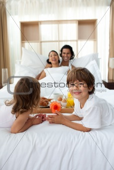 Happy children bringing a breakfast to their parents 