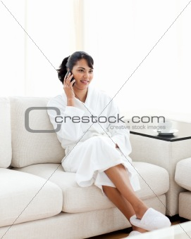 Young woman on phone sitting on the sofa
