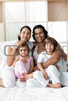 Portrait of a happy family sitting on a bed at home