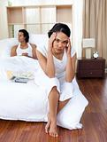 Angry couple sitting separately on their bed after an argument