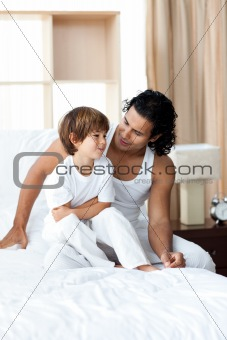 Adorable little boy talking with his father