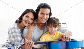Caring parents playing guitar with their son