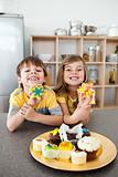 Cute siblings showing their cookies