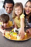 Joyful family eating cookies