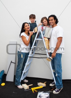 Merry parents with their children painting a room in their house