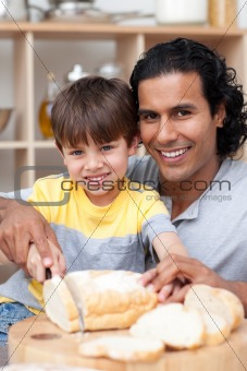 Attentive father helping his son cut some bread in the kitchen