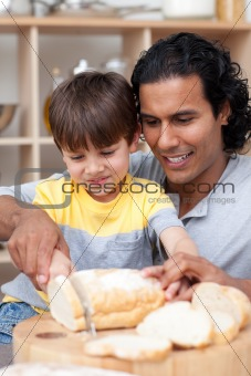 Attractive father helping his son cut some bread