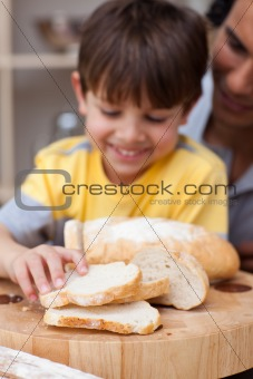 Adorable little boy eating bread with his father
