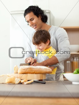 Attentive father helping his son cut some bread