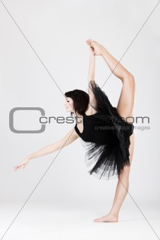 Beautiful female ballerina doing split against white