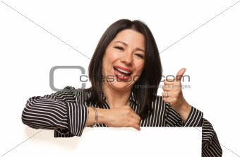 Attractive Smiling Multiethnic Woman Leaning on Blank White Sign with Thumbs Up Isolated on a White Background.