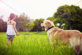 Young girl with golden retriever walking away