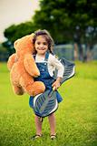 Cute girl standing in the grass holding teddy bear