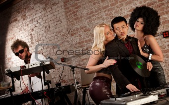 Pretty ladies surrounding a DJ