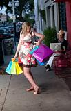 Pregnant woman with bags struggling to reach her purse