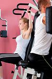 young woman doing back exercise on a machine in modern gym