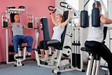 three people exercising on machines at modern gym - health club