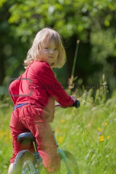 boy with long blond hair riding a bike in the garden