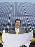 businessman standing near solar panels